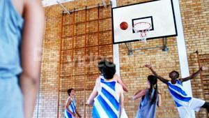 School students playing basketball in basketball court