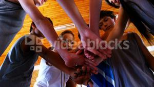 Sports teacher and school students forming hand stack in basketball court