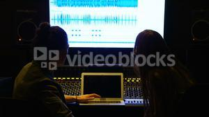 Audio engineers using laptop while mixing sound