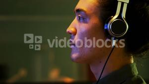 Male audio engineer listening to headphones while mixing sound