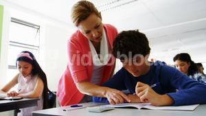 Teacher helping students with their classwork