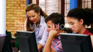 Teacher assisting students in computer class