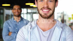 Portrait of happy male executives standing with arms crossed