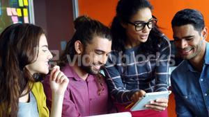 Smiling graphic designers discussing over digital tablet in meeting