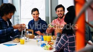 Happy executives interacting while having breakfast