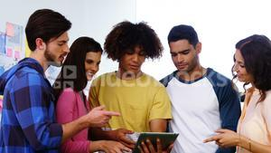 Smiling graphic designers discussing over digital tablet during meeting
