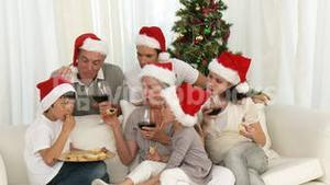Happy family drinking wine and eating sweets at Christmas