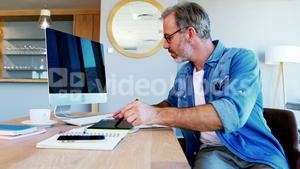 Male graphic designer using graphic tablet at desk