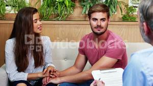 Couple holding hands while consulting doctor