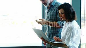 Male and Female executives using laptop near the window