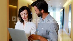 Male and Female executives using laptop in corridor