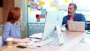 Male and female executives working together at desk