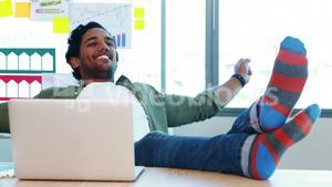 Male executive relaxing with feet up at desk