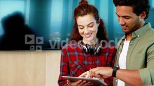 Male and female executives discussing over digital tablet