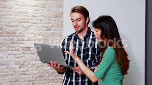 Male and female executives discussing over laptop