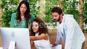 Team of executives discussing over computer at desk