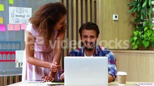 Two executives discussing over laptop at desk
