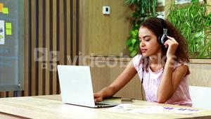 Female executive listening to music while using laptop