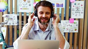 Executive listening to music while using laptop