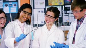 Smiling school kids doing a chemical experiment in laboratory
