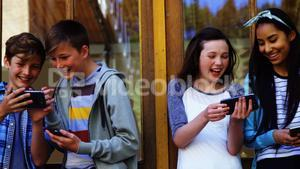 Group of school friends using mobile phone outside school