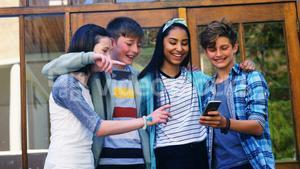 Smiling schoolkids looking photos on mobile phone