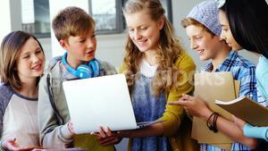 Group of students using laptop in classroom