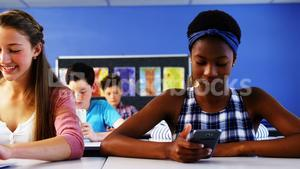 Students using laptop and mobile phone in classroom