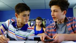 Student using mobile phone in classroom