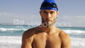Portrait of male surfer standing with arms crossed in the beach