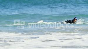 Male surfer swimming in the beach