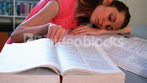 Tired schoolgirl leaning on desk in library