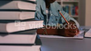 Close-up of book stack with schoolboy studying in background