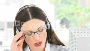 Woman speaking to a customer on a headset in the office