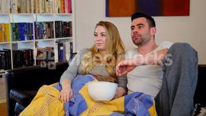 Couple relaxing on sofa watching tv in living room