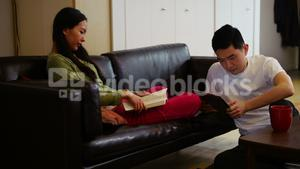 Woman reading book while man using digital tablet in living room