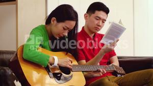 Couple playing guitar in living room