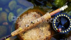 Fly fishing rod, reel and hook on rock
