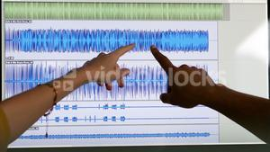 Two people pointing at music waves on the screen