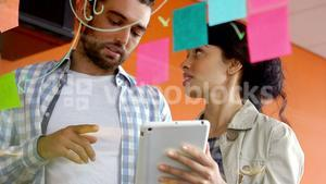 Male and female executive discussing over digital tablet