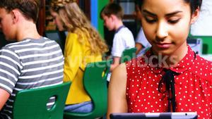 Schoolgirl using digital tablet while other students studying on computer in classroom