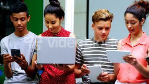 Students using laptop, mobile phone and digital tablet