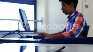 Schoolboy studying on computer in classroom