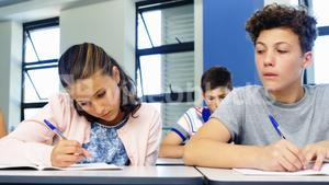 Schoolboy cheating during exam in classroom
