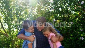 Father embracing his kids in park
