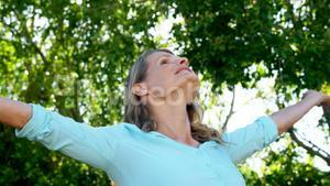 Happy woman standing with hands raised in park