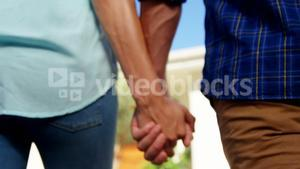 Mid section of couple walking hand in hand in house garden