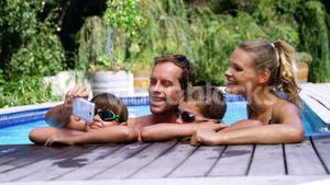 Happy family using mobile phone near poolside