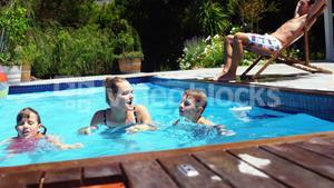 Mother and kids swimming in pool