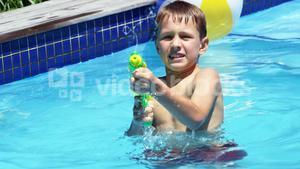 Happy family doing water gun battle in swimming pool